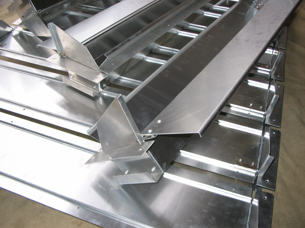 Chicken house ventilation ducts bespoke fabricated from sheet aluminium, with stainless steel hinges.