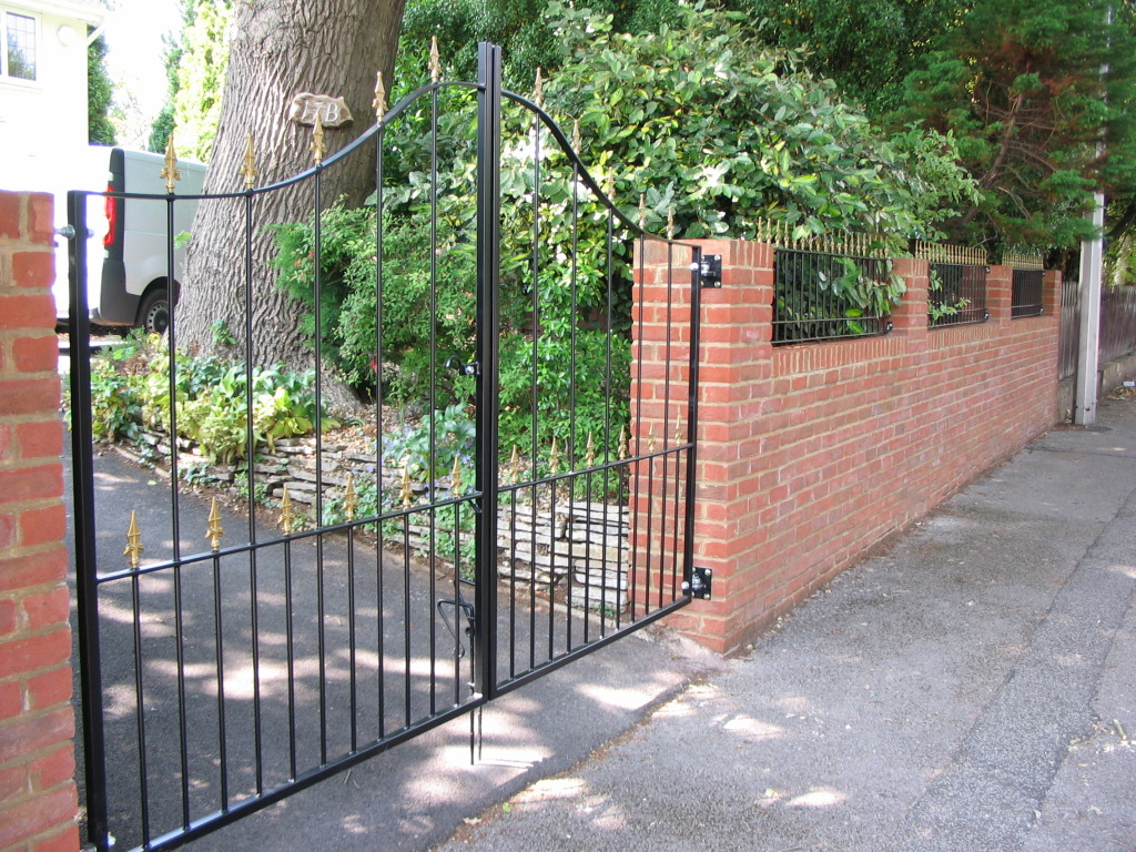 Bespoke fabricated mild steel arched drive gates and railings with gold coloured rail heads. Bournemouth.